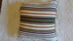 Cojín beis con colorides de tejido alpujarreño para un sillón, silla o cama